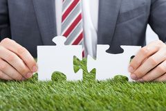 Businessman joining puzzle pieces on grass Royalty Free Stock Images