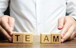 A businessman joins together two parts of the word Team. personnel management, the organization and creation of working groups. And teams, the creation of links stock images