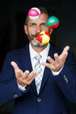 Businessman juggles balls Stock Photos