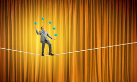 Businessman juggling with balls. Young businessman balancing on rope and juggling with balls Stock Photography