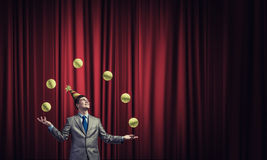 Businessman juggling with balls. Young businessman in cap on stage juggling with balls Royalty Free Stock Photo