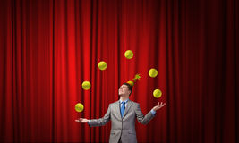 Businessman juggling with balls. Young businessman in cap on stage juggling with balls Stock Photo