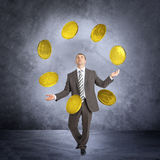 Businessman juggling big coins Royalty Free Stock Photo