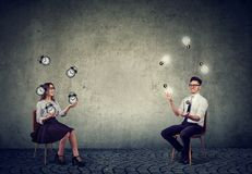Business man juggling with idea light bulbs with business woman managing time and efficiency stock photography