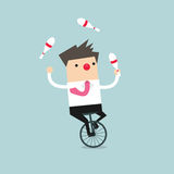 Businessman juggling while cycling with red nose Stock Photo
