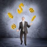 Businessman juggling dollar sign Stock Image