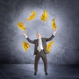 Businessman juggling euro sign Stock Images