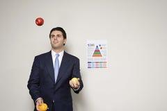 Businessman juggling fruit Stock Photo