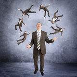 Businessman juggling little people Royalty Free Stock Photos