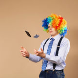 Businessman juggling mobile phones. Close-up Portrait of business man in clown wig. Business concept Stock Photography