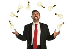 Businessman Juggling Multiple Lightbilbs. Hispanic businessman juggling multiple lightbulbs isolated over white background stock photo
