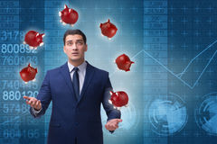 The businessman juggling with piggybanks in business concept. Businessman juggling with piggybanks in business concept Royalty Free Stock Image