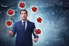 The businessman juggling with piggybanks in business concept Royalty Free Stock Photo