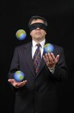 Businessman juggling with planet earth. With dark background-Vertical Royalty Free Stock Photos