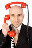 Businessman Juggling Two Calls. Businessman on phone juggling two calls at the same time Royalty Free Stock Photo
