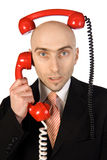 Businessman Juggling Two Calls. Businessman on phone juggling two calls at the same time Royalty Free Stock Photography