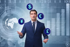 The businessman juggling between various currencies Stock Photo