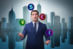 The businessman juggling between various currencies Royalty Free Stock Photography