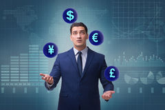 The businessman juggling between various currencies Royalty Free Stock Photo
