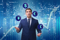 The businessman juggling between various currencies Royalty Free Stock Images