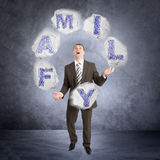 Businessman juggling word family Royalty Free Stock Images