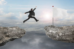 Businessman jump on cliff with blank flag and sunlight cloudscap Royalty Free Stock Image