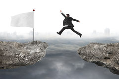 Businessman jump on cliff with white flag and cloudy cityscape Royalty Free Stock Image