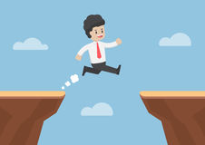Businessman Jump Through the Gap Between Cliff Stock Photos