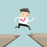 Businessman jump through the gap from one cliff to another Stock Images