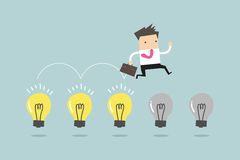 Businessman jump on light bulbs Royalty Free Stock Images