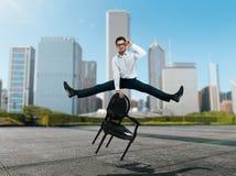 Businessman jump over chair against skyscrapers. Young businessman in glasses jump over chair against skyscrapers. Succuss business concept Stock Photo