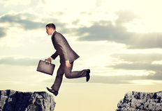 Businessman jumped over abyss Stock Image