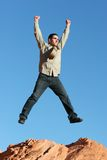 Businessman jumping. Successful businessman jumping on red rocks Royalty Free Stock Images