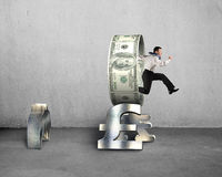 Businessman jumping through circle on stack money symbols Royalty Free Stock Photo