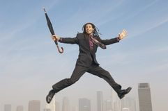 Businessman Jumping With Closed Umbrella Royalty Free Stock Images