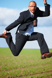 Businessman jumping in a field-success Royalty Free Stock Photography