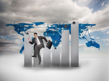 Businessman jumping in front of a chart and a world map Stock Photo