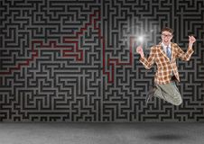 Businessman jumping in front of digitally generated maze wall. Excited businessman jumping in front of digitally generated maze wall Royalty Free Stock Images