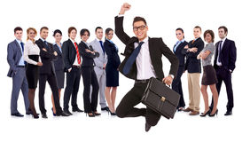 Businessman jumping in front of his team stock images