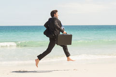 Businessman jumping in front of the sea Stock Images