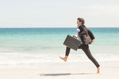 Businessman jumping in front of the sea Royalty Free Stock Image