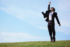 Businessman jumping on grass stock images