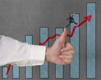 Businessman jumping on growing red arrow with thumb up Stock Photo