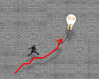 Businessman jumping on growth red arrow with glowing lamp balloo Royalty Free Stock Photography
