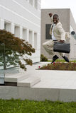 Businessman jumping of happiness. Outside his office Stock Images