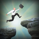 Businessman jumping from high cliff. stock images