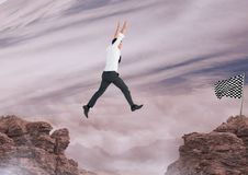 Businessman jumping with his hands up to catch the checker flag Stock Photo