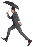 Businessman jumping holding an umbrella Royalty Free Stock Images