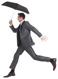 Businessman jumping holding an umbrella Stock Image