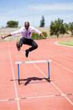 Businessman jumping a hurdle while running Royalty Free Stock Photo